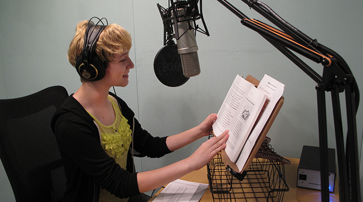 A volunteer in the recording booth at ABLE.