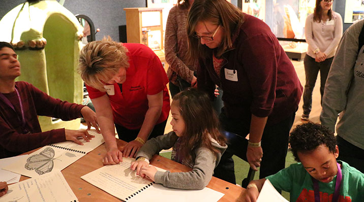 Blind role models from the community serve as mentors for young braille users, illustrating the use of braille in everyday life.